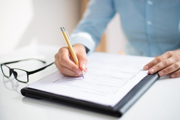 Primo piano della donna di affari che fa le note nel documento Foto Gratuite