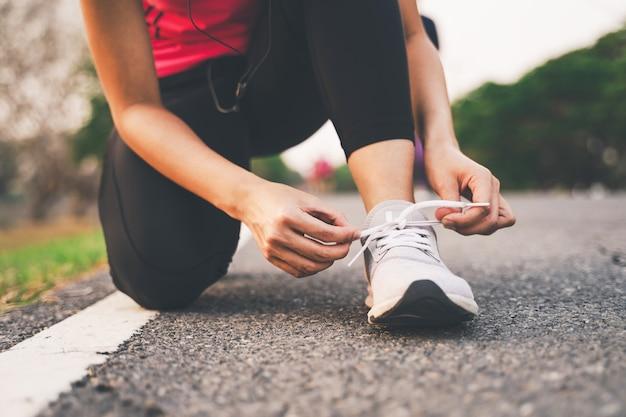 Primo piano della donna di forma fisica che lega i laccetti nel parco durante il tramonto Foto Premium
