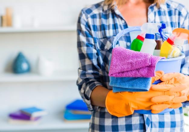Primo piano della donna in guanti di gomma che tengono secchio delle attrezzature per la pulizia Foto Gratuite