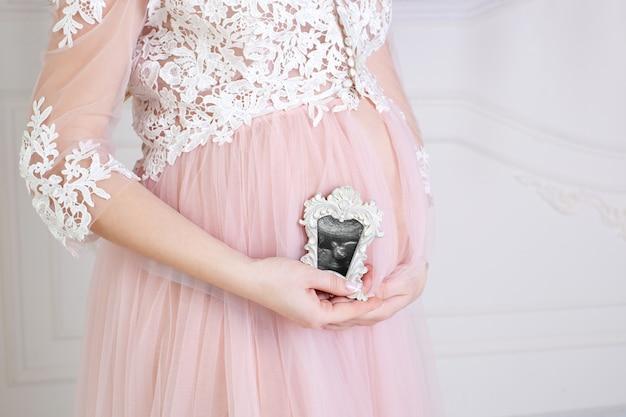 Primo piano della donna incinta che tiene un'ecografia sulla sua pancia. la donna incinta gode della prima foto del suo bambino non ancora nato nella cornice Foto Premium