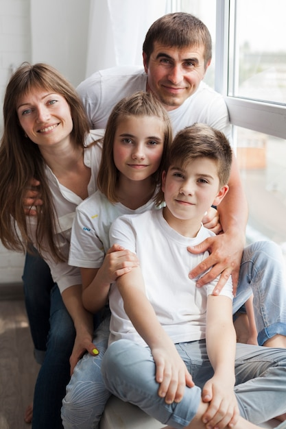 Primo piano della famiglia sorridente che si siede sul davanzale della finestra a casa Foto Gratuite