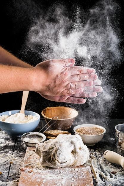 Primo piano della farina della spolverata della mano del panettiere sulla pasta con gli ingredienti sulla tavola Foto Gratuite