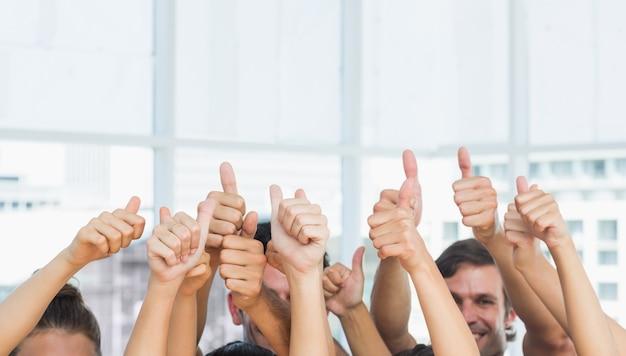 Primo piano della gente potata che gesturing i pollici su Foto Premium