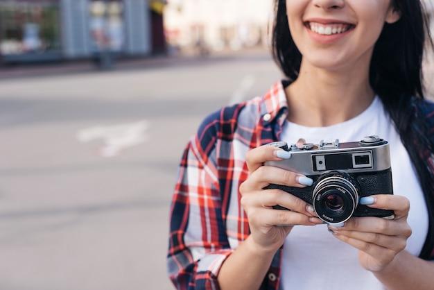 Primo piano della giovane donna sorridente che tiene retro macchina fotografica all'aperto Foto Gratuite
