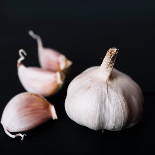 Primo piano della lampadina dell'aglio su fondo nero Foto Gratuite