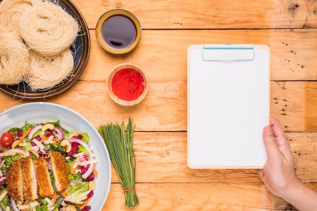 Primo piano della lavagna per appunti della tenuta della mano di una persona vicino all'alimento tailandese tradizionale sulla tavola di legno Foto Gratuite