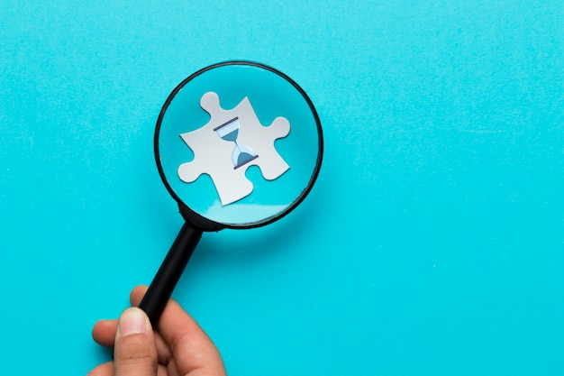 Primo piano della lente d'ingrandimento della tenuta della mano di una persona sopra l'icona di vetro di ora sul puzzle bianco sopra il contesto blu Foto Gratuite