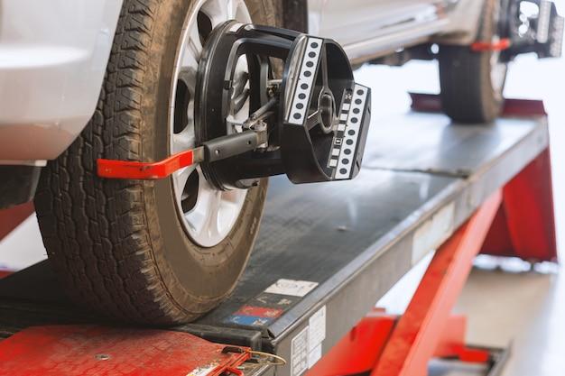 Primo piano della macchina d'equilibratura della ruota al centro di servizio della gomma Foto Premium