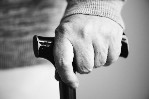 Primo piano della mano anziana che tiene un bastone da passeggio Foto Gratuite