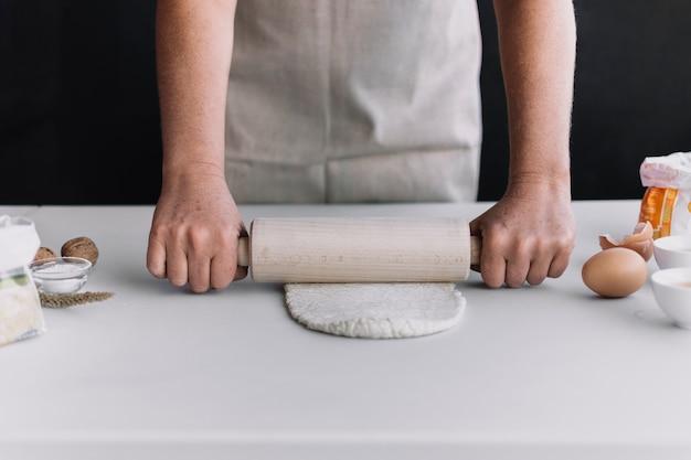 Primo piano della mano appiattimento di una persona con mattarello sul bancone della cucina Foto Gratuite