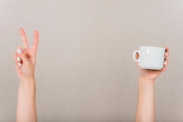 Primo piano della mano che fa il gesto di pace e tazza bianca contro il contesto colorato Foto Gratuite