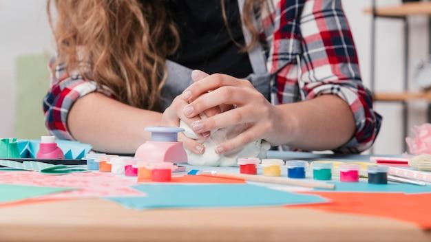 Primo piano della mano che impastano argilla bianca per il mestiere creativo Foto Gratuite