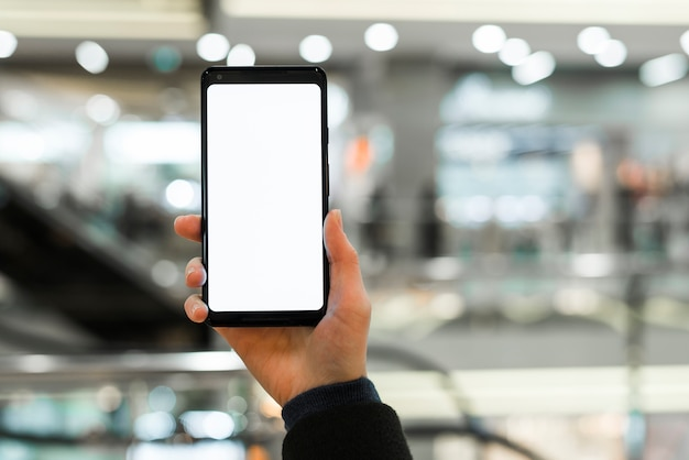 Primo piano della mano che mostra esposizione in bianco bianca dello smart phone in centro commerciale Foto Gratuite