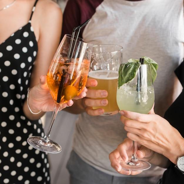 Primo piano della mano degli amici che tiene vetro delle bevande Foto Gratuite