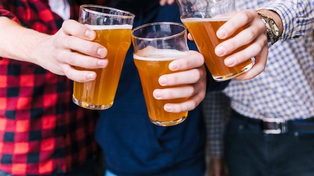 Primo piano della mano degli amici tintinnio dei bicchieri da birra Foto Gratuite