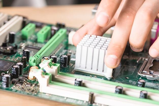 Primo piano della mano del tecnico maschio che installa il dissipatore di calore sulla scheda madre del computer Foto Gratuite
