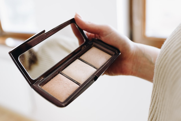Primo piano della mano del truccatore professionista o mua è in possesso di una tavolozza di cosmetici ombretto. donna caucasica con l'ombra compatta. Foto Premium