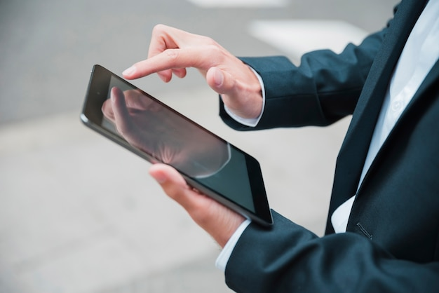 Primo piano della mano dell'uomo d'affari utilizzando la tavoletta digitale Foto Gratuite
