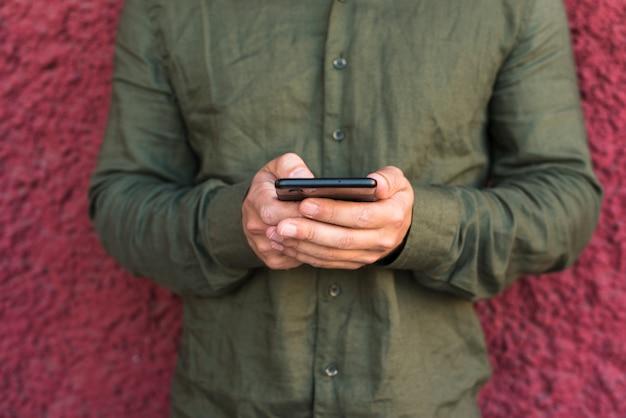 Primo piano della mano dell'uomo tramite cellulare Foto Gratuite