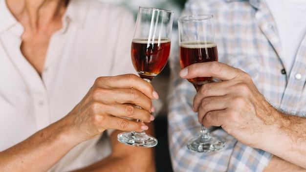 Primo piano della mano della coppia senior che tosta i vetri di vino Foto Gratuite