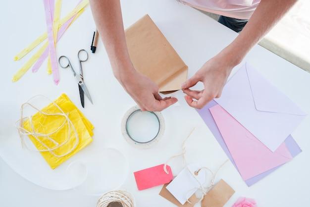 Primo piano della mano della donna che avvolge il contenitore di regalo sulla tavola Foto Gratuite