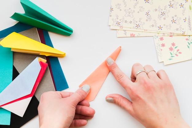 Primo piano della mano della donna che fa aeroplano di carta con carte colorate sullo scrittorio bianco Foto Gratuite