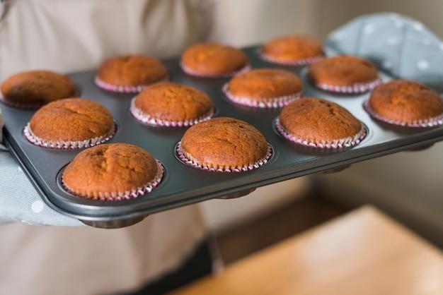 Primo piano della mano della donna che tiene i muffin al forno nel vassoio di cottura Foto Gratuite