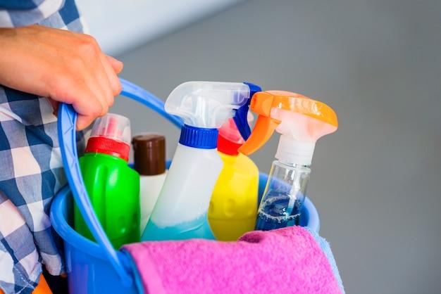 Primo piano della mano della donna che tiene secchio blu con attrezzature per la pulizia Foto Gratuite