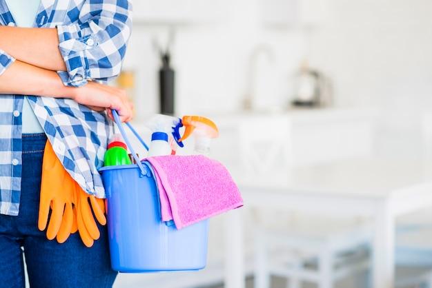 Primo piano della mano della donna che tiene secchio con prodotti per la pulizia e tovagliolo rosa Foto Gratuite