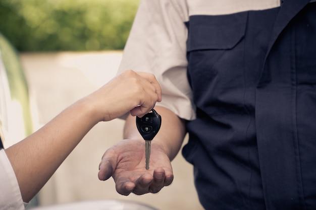 Primo piano della mano della donna sta inviando le chiavi della macchina al meccanico. Foto Premium