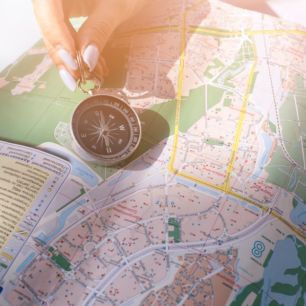 Primo piano della mano della femmina che tiene bussola di navigazione sulla mappa Foto Gratuite