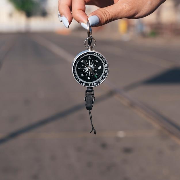 Primo piano della mano della femmina che tiene bussola di navigazione Foto Gratuite