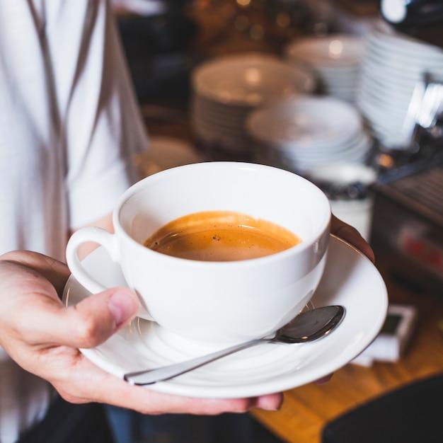 Primo piano della mano della persona che tiene tazza di caffè delizioso Foto Gratuite