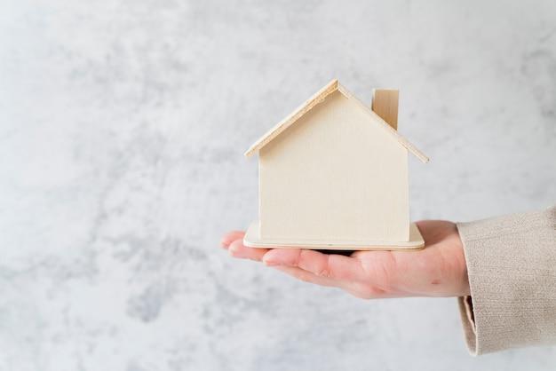 Primo piano della mano della persona di affari che tiene il modello di casa in miniatura in legno contro il muro di cemento bianco Foto Gratuite