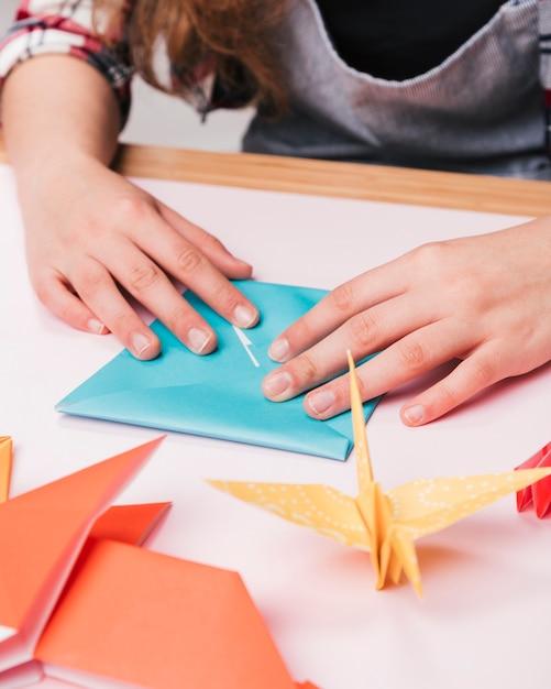 Primo piano della mano di donna pieghevole carta origami per fare mestiere creativo Foto Gratuite