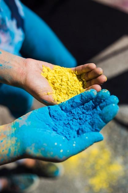 Primo piano della mano di due donne che tiene il colore giallo e blu di holi Foto Gratuite