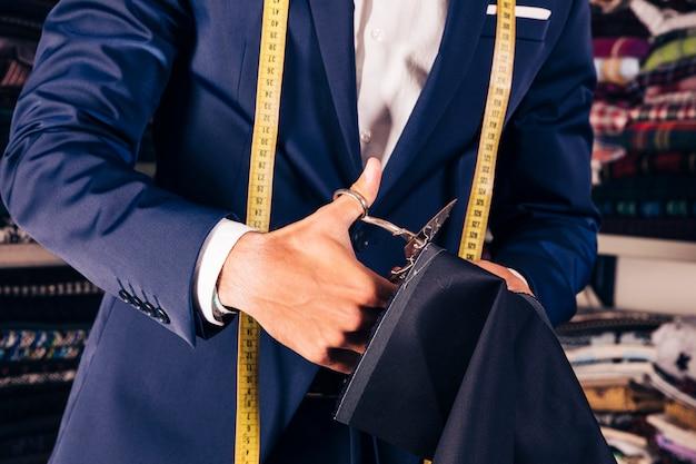 Primo piano della mano di un designer di moda maschile che taglia il tessuto con le forbici Foto Gratuite