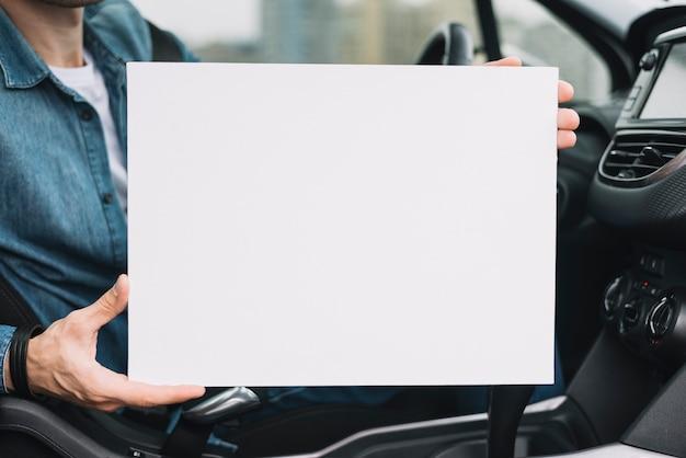 Primo piano della mano di un uomo che mostra cartello bianco bianco Foto Gratuite