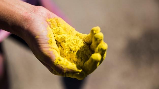 Primo piano della mano di un uomo che tiene il colore giallo holi Foto Gratuite