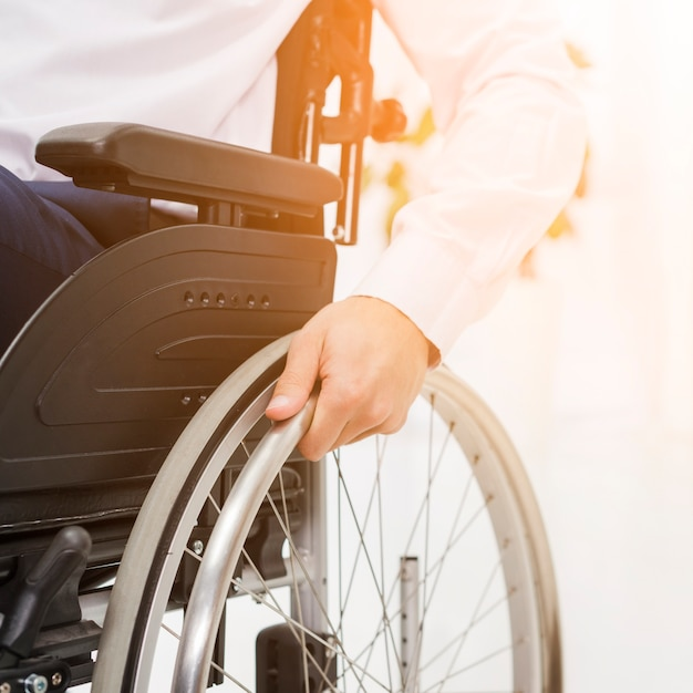 Primo piano della mano di un uomo d'affari sulla ruota della sedia a rotelle Foto Gratuite