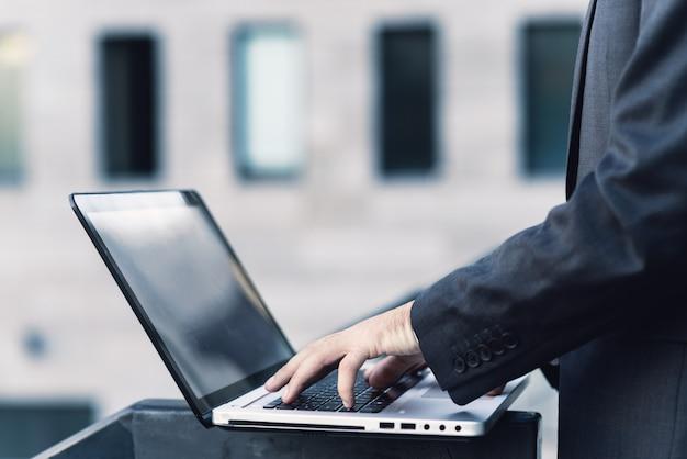 Primo piano della mano di un uomo in un vestito. stampa sulla tastiera di un laptop Foto Premium