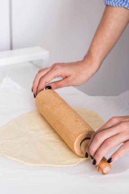 Primo piano della mano di una donna che appiattisce la pasta con il matterello sulla carta pergamena Foto Gratuite