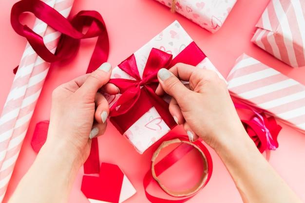 Primo piano della mano di una donna che lega il nastro rosso sul contenitore di regalo sopra il contesto rosa Foto Gratuite