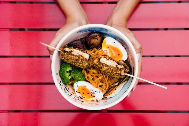Primo piano della mano di una donna che tiene ciotola di spaghetti ramen con uovo; cipolla e broccoli su rosso Foto Gratuite