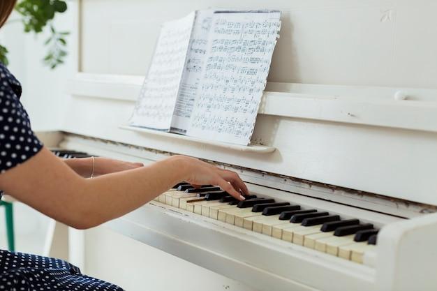 Primo piano della mano di una femmina che suona il pianoforte Foto Gratuite