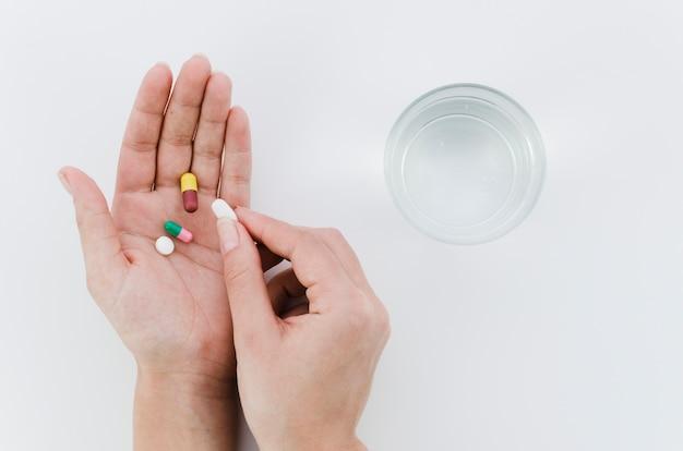 Primo piano della mano di una persona che cattura le pillole con bicchiere d'acqua sul contesto bianco Foto Gratuite