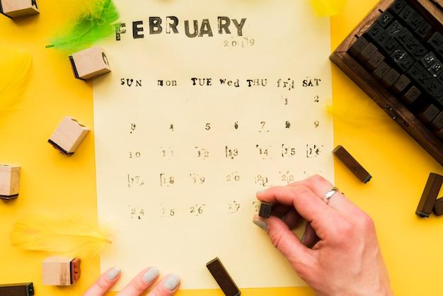 Primo piano della mano di una persona che rende il calendario di febbraio fatto a mano con blocchi tipografici Foto Gratuite