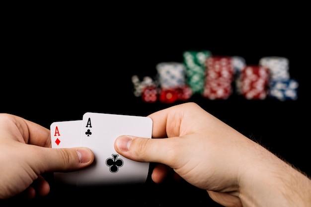 Primo piano della mano di una persona che tiene due carte da gioco di assi Foto Gratuite