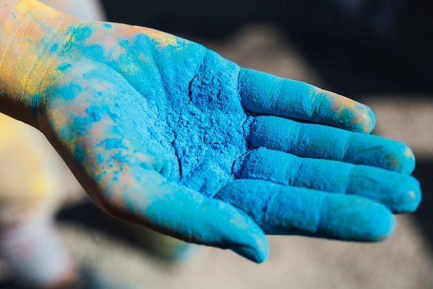 Primo piano della mano di una persona che tiene il colore blu di holi Foto Gratuite