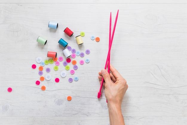 Primo piano della mano di una persona che tiene l'ago a maglia con rocchetto e bottoni sullo sfondo texture Foto Gratuite
